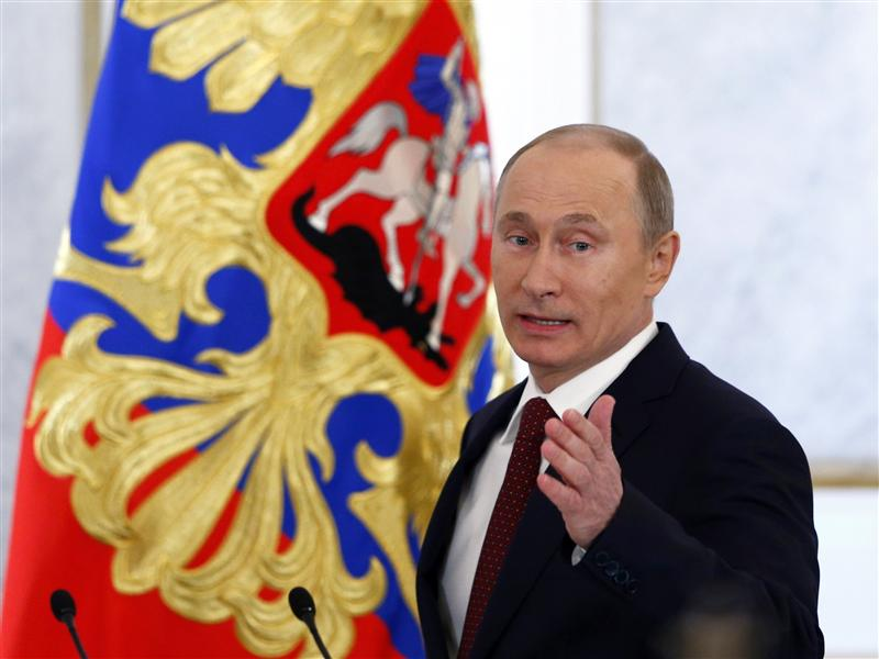 Russia's President Vladimir Putin gestures as he walks in before making his annual state of the nation address at the Kremlin in Moscow