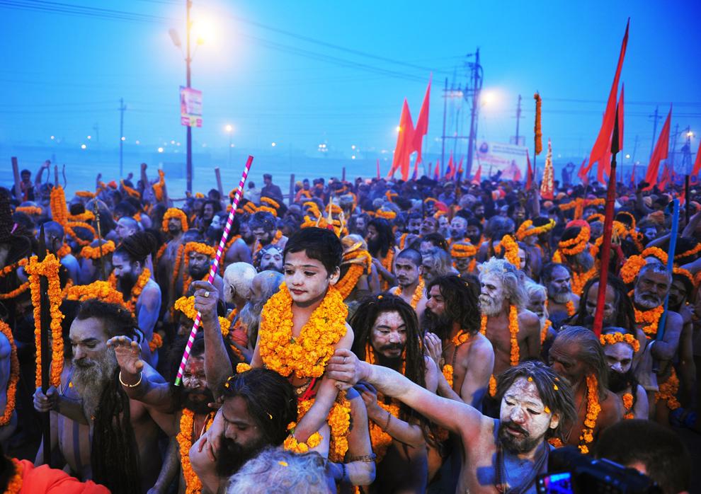 Copil purtat pe umeri de Sadhu, in cadrul festivalului Maha Kumbh Mela