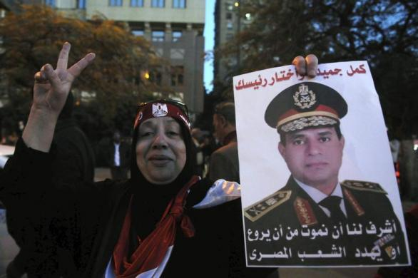 An Egyptian holds an image of Egypt's Army Chief General Abdel Fattah al-Sisi during a protest against what they say is Qatar's backing of ousted Egyptian president Mohamed Mursi's government, outside the Qatari Embassy in Cairo