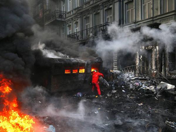 Un protestatara arunca anvelope in foc, in timpul luptelor violente cu fortele de ordine din centrul Kievului
