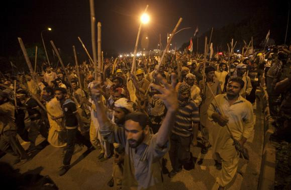 Supporters of ul-Qadri carry sticks as they move towards the Prime Minister's house during the Revolution March in Islamabad