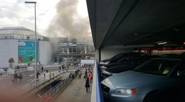 Fumul iese dintr-una din clădirile aeroportului din Bruxelles după două explozii care au avut loc la terminalul plecări în dimineața de 22 martie