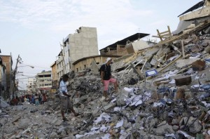 Residents walk on debris of a collapsed hotel after an earthquake struck off the Pacific coast, in Portoviejo, Ecuador