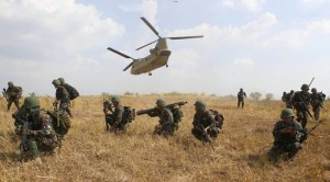 "Filipino soldiers take positions as a U.S. military helicopter CH-47 takes off during the annual ""Balikatan"" war games at a military camp, Fort Magsaysay"