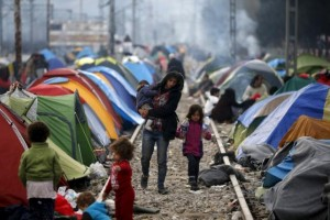 Migrants walk on a railway track at a makeshift camp on the Greek-Macedonian border, near the village of Idomeni
