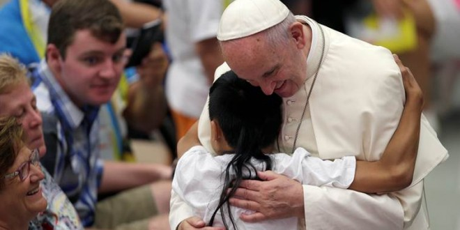 A sick child greets Pope Francis during the weekly audience in Paul VI hall at the Vatican