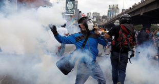 Demonstrator throws a tear gas canister back to policemen during an opposition rally in Caracas